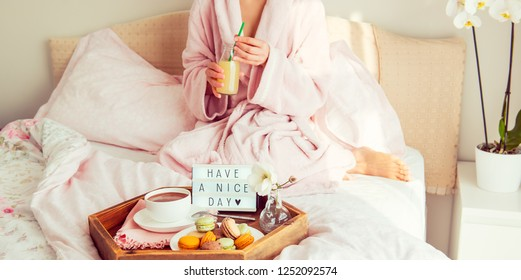Good morning concept. Breakfast in bed with Have a nice day text on lighted box, coffee and macaroons on tray and blurred woman in bathrobe drinking juice. Hospitality, care, service. Copy space