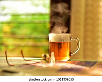 Good morning concept. A clear glass cup of hot, steaming black tea, newspaper and reading glasses. Morning cuppa. Concept of routine habits.