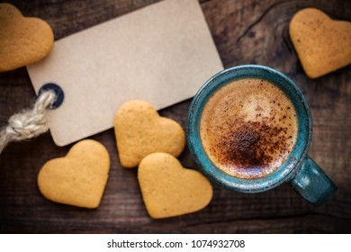 Good morning concept with cup of espresso coffee, heart shape cookies and an empty tag on rustic wooden table