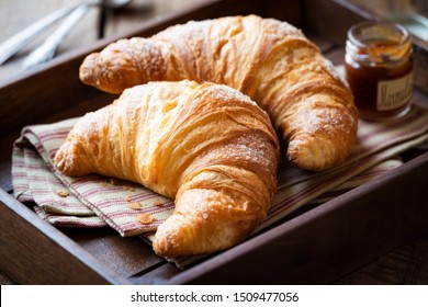 Good morning concept - Freshly baked croissants on a tray with a small jar of jam for breakfast