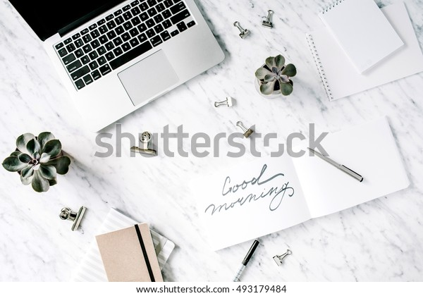 Good morning. Flat lay, top view office table desk. Workspace with laptop, diary, succulent and clips on marble background.