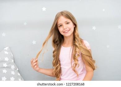 Good morning. Girl child long curly hair awake. Pleasant awakening. Girl looks cheerfully and full of energy in morning. Tips having pleasant morning every day. Enjoy awakening and feel good.