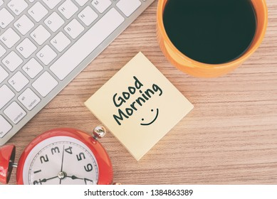 Good morning greeting on paper note with computer keyboard, coffee and alarm clock pointing at 7 o'clock.