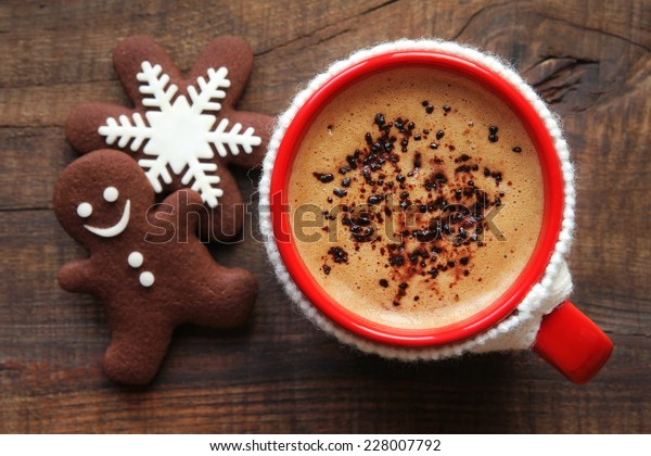 Good morning or Have a nice day Merry Christmas message concept - red cup of frothy coffee in knitted cup holder and traditional decorated festive snowflake and gingerbread man chocolate cookies
