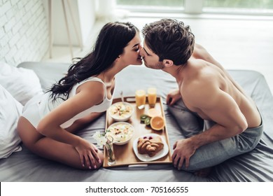 Good morning! Healthy breakfast in bed. Young beautiful love couple is sitting in bed before having breakfast.