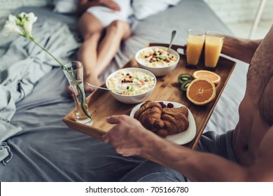 Good morning! Healthy breakfast in bed. Beautiful young woman is lying in bed while her handsome man bringing tasty breakfast.