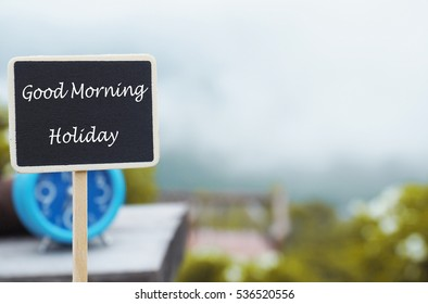 Good morning holiday message on wood board on nature morning mist background