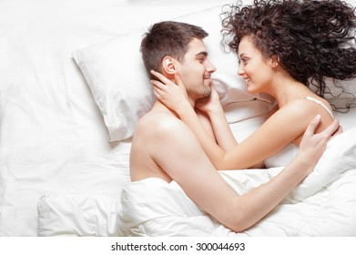 Good morning! Love and comfort. Overhead of happy beautiful young couple lying on the bed laughing and hugging. Top view.