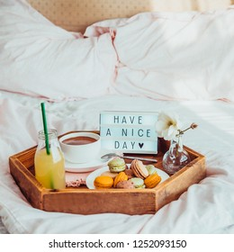 Good morning mood decor. Start a New day. Breakfast in bed with Have a nice day text on lighted box. Cup of coffee, juice, macaroons, flower in vase on wooden tray. Hospitality, care, service concept.