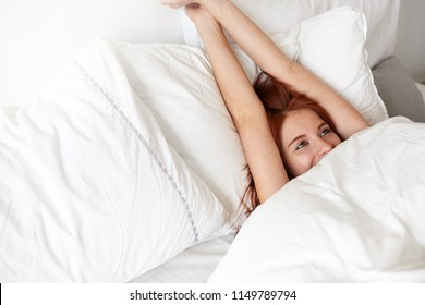 Good morning. Playful charming young woman with ginger hair lying in bed under white cover, stretching, raising arms, having great plans for day. Cute girl lazing in her bedroom, smiling happily