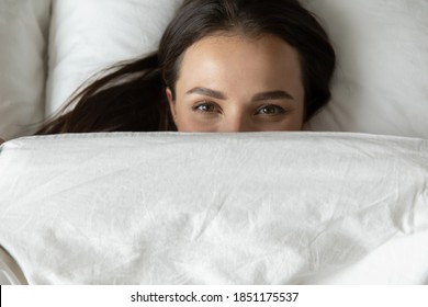 Good morning! Portrait of happy joyful young female resting relaxing lying in bed and looking at camera covering half of face with blanket and peering out with fun in eyes joking playing having fun