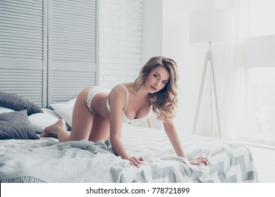 Good morning! Portrait of sexy pretty girl of a dream in doggy style and white underwear on bed with ideal figure in light room making provocarion for him on valentine day 14 february