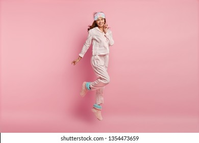 Good morning! Positive young European woman in nightwear, eyemask, jumps in air, has glad expression, has energy after awakening, isolated over pink background. People, bed time and rest concept