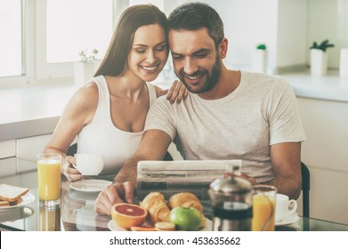 Good morning starts with good news. Beautiful young couple bonding to each other and reading newspaper together while sitting in the kitchen and having breakfast