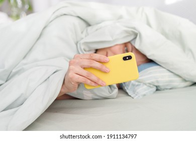 good morning, sunny day woman checking messages. womans hand holding phone up, with yellow phone in bed under blanket, morning starts with checking messages from friends and work online