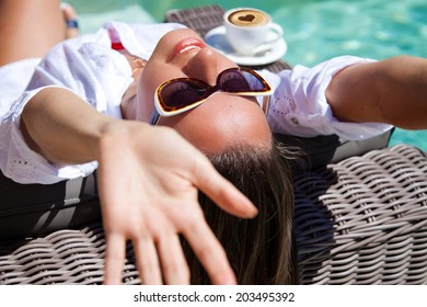 Good morning at vacation, women with hands up. Portrait of pretty cheerful woman relaxing at the poolside with morning coffee, sunny day, outdoor
