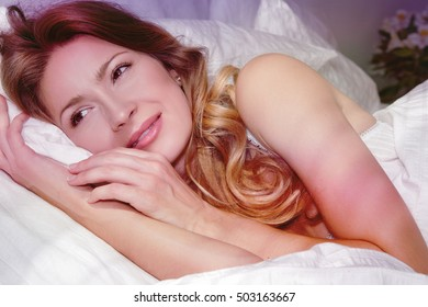 Good morning. WOMAN woke up in bed. Rest, sleeping, comfort and people concept - young woman stretching in bed at home bedroom, a young woman in the early morning. Comfortable bed, relaxing in his bed