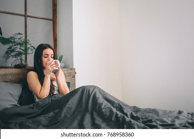 Good morning! Woman woke up in bed. Woman drinking coffee in bed