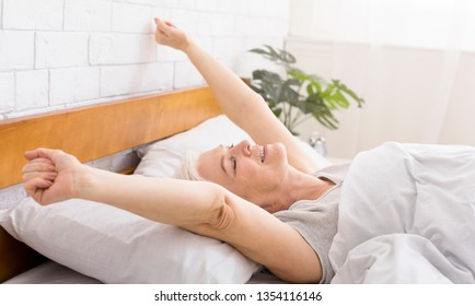 Good morning, world. Well slept senior woman stretching in bed, waking at home