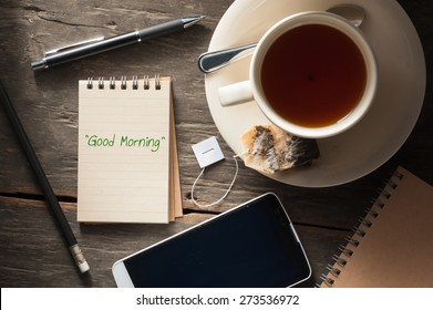 """Good morning"" is written on small notepad with a cup of tea, pen, pencil and cellphone on rustic wood background with low key scene"