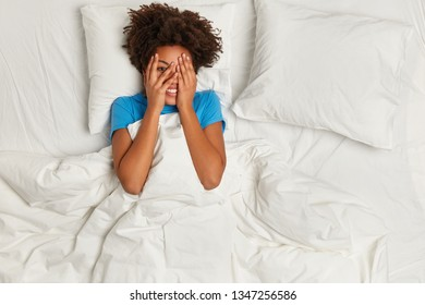 Good morning to you! Playful cheerful shy Afro woman covers face with both hands, peeks through fingers dressed in blue t shirt basks in bed under white bedclothes satisfied after night with boyfriend