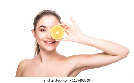 Good for my skin. young attractive woman holding an piece of orange and smiling at the camera.