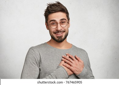 Good natured attractive young stylish hipster guy has friendly expression, keeps hands on heart, expresses his feelings to girlfriends, shows love and great sympathy, isolated over concrete white wall
