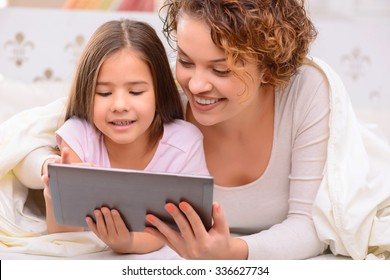 Good news. Cheerful elated delighted mother and daughter lying on  bed  and holding laptop while surfing the Internet