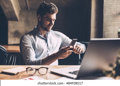 Good news from colleague. Confident young man in smart casual wear holding smart phone and looking at it while sitting at his working place in office