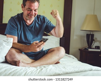 Good news concept. Happy man with smartphone on the bed rejoices.