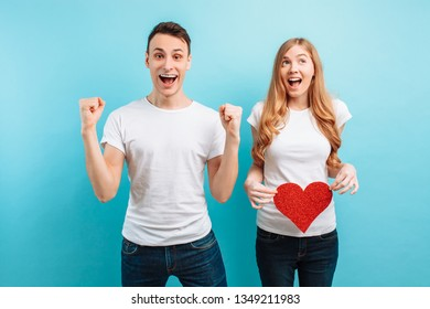 Good news An enthusiastic man, showing a gesture of victory, learns about his wife's pregnancy, is ready to become a father. pregnant woman holding red paper heart against belly, on blue background.