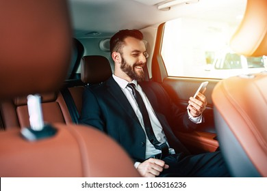 Good news! Handsome smiling business man with mobile phone on hand in car