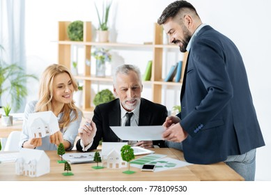 Good news. Professional real estate agents feeling satisfied with the results of their work while sitting in their comfortable equipped office and looking at the important document