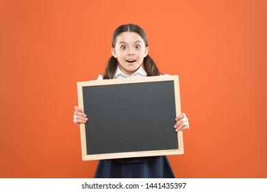 Good news for pupils community. Educational program. School schedule information. School girl cute pupil hold blackboard copy space. School announcement concept. Informing kids changes in school life.