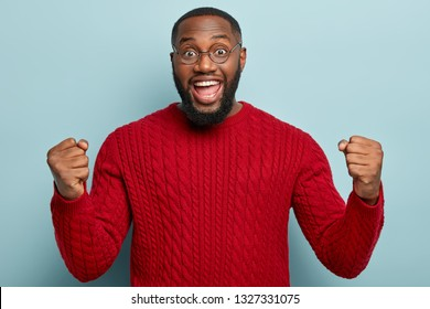 Good news, success and happiness concept. Ecstatic overjoyed black plump man with thick bristle, clenches fists in triumph, recieves expensive present, wears red jumper, glad to win lottery.