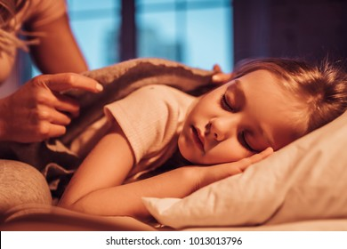 Good night, princess! Attractive young woman with little cute girl are spending time together at home. Mom is putting daughter to bed. Happy family concept. Mother's day.