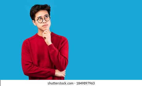 Good Offer. Portrait of pensive asian man in glasses looking up at copy space, touching his chin, isolated over blue studio background. Thoughtful teen guy thinking and making decision