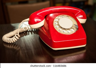 A good old fashioned red telephone, over a wooden table, makes people remember the 70`s or 80`s