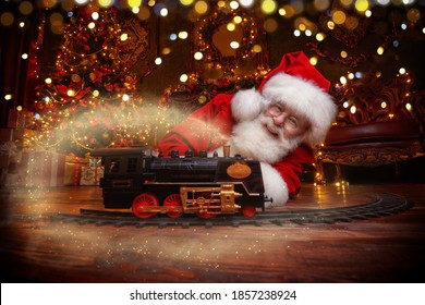 Good old Santa Claus brought gifts for Christmas and sat down to play a steam train in a beautiful Christmas interior. Magic lights sparkling around.