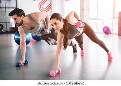Good picture of boy and girl standing on the carpet with the dumbells in one hand and putting another hand with a dumbell behind the back