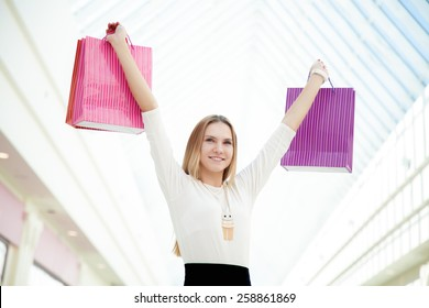 Good purchases, happy mood, joyful young woman delighted with her shopping, holding pile of paper bags. Sale, discount, fashion, profitable offer concepts