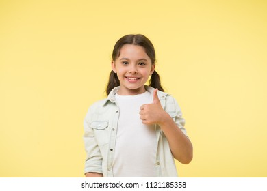 Good quality. Kid girl shows thumb up gesture recommends yellow background. Child highly recommend with thumb up gesture. Girl happy smiling recommend high quality product. Make right choice.
