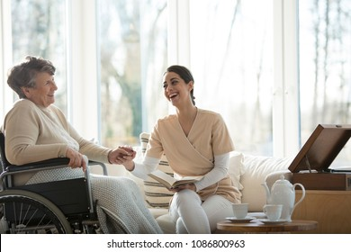 Good relationship between smiling nurse and happy disabled elderly woman in the nursing home