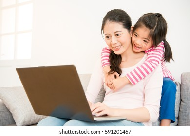 good relationship mother and little cute girl daughter looking at laptop together seated on sofa in the living room at home. family activity concept.