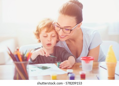 Good results. Smiling pretty young mother teaching her toddler son to draw while helping him and feeling happy.