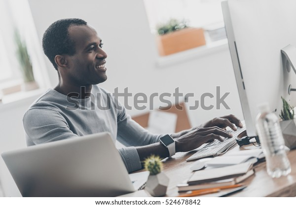 Good results! Young IT Professional working on the computer and smiling while sitting at his working place in home office