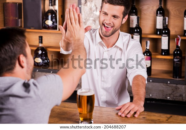 It is good to see you again! Rear view of male customer talking to bartender while sitting at the bar counter