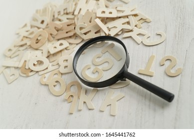Good and Service Tax (GST) with many alphabet word and magnifier. The images blurring, Magnifier focusing and at subject of word GST.  The background of wood. top view