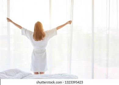 a good shape and healthy young girl wake up in the morning at sunrise and standing and stretching at window in bedroom