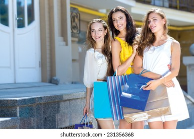 Good shopping mood. Three young and pretty girls are standing with shopping bags, looking forward and smiling